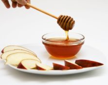 Apple slices and bowl of honey on a plate